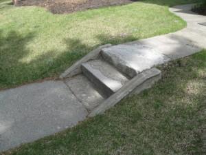 A narrow,  broken concrete side walk