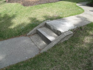 A narrow,  broken concrete side walk