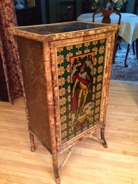 This small cupboard with shelves is constructed with bamboo and wood and embellished with textured wallpaper.